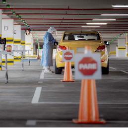 Persona realizando prueba PCR a un conductor de taxi